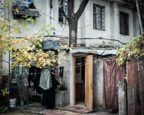 Binanın sakinlerinden biri, girişteki çeşmede kıyafetlerini yıkıyor
