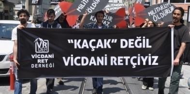 """Davut Erkan (solda) vicdani ret eyleminde, """"Kaçak değil vicdani retçiyiz"""" pankartını taşırken."""