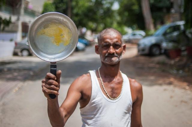 Hindistan'ın Yeni Delhi kentinde 49 yaşındaki Ajay Adav, asfaltta pişirdiği omleti gösteriyor